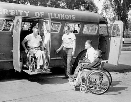 two men in wheelchairs exiting a bus in the 1950s