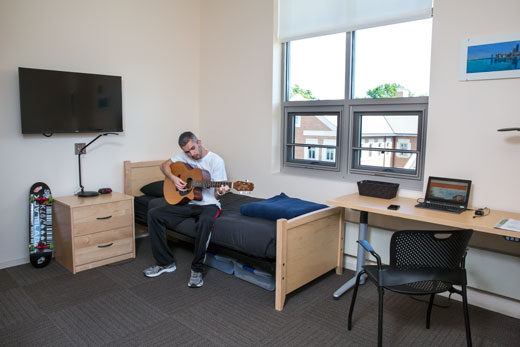 man playing guitar sitting on edge of his bed, window behind him