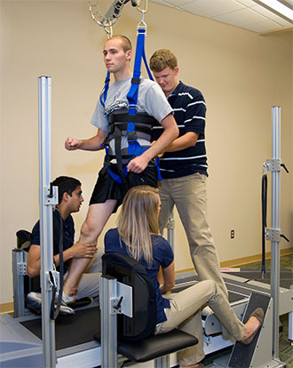 Man walking on treadmill while supported by harness, getting physical therapy from two therapists