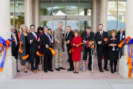 12 dignitaries cut ribbon in front of the Center for Wounded Veterans