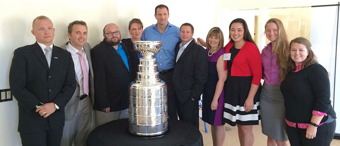 10 staff members posing around the Stanley Cup trophy